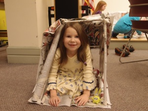 A girl kneels in the newspaper structure she built
