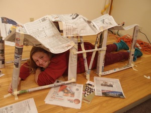 A girl lies in the newspaper structure she built