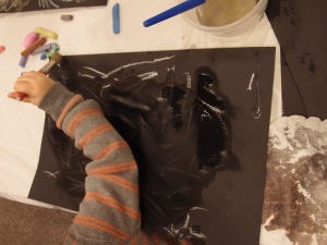 A child draws with chalk and water