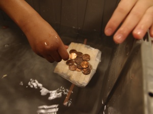 A child adding pennies to the boat they built out of popsicle sticks and wax paper