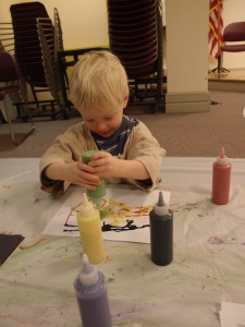 Boy squeezing paint from a bottle