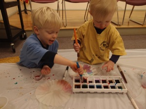 Two children play with water colors